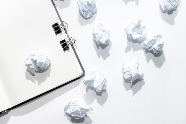 Notepad on a white background with scattered crumpled notes