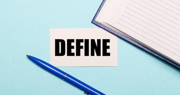 Блокнот, белая ручка и карточка с надписью define на синей поверхности. вид сверху.