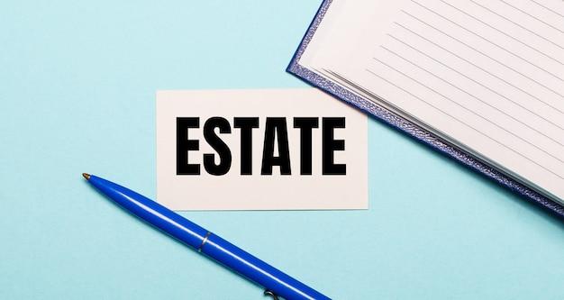 Блокнот, белая ручка и карточка с надписью estate на синем фоне. вид сверху