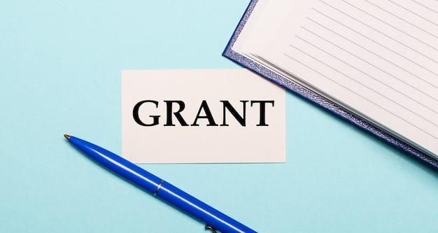 Блокнот, белая ручка и карточка с надписью grant на синей стене. вид сверху