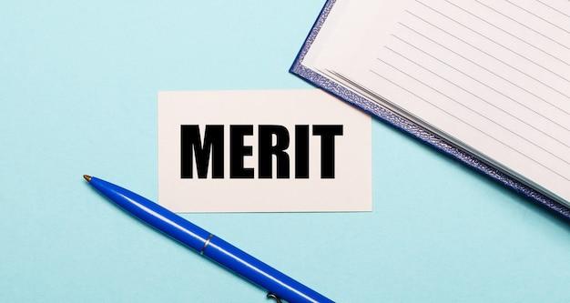 メモ帳、白いペン、青い背景にmeritと書かれたカード