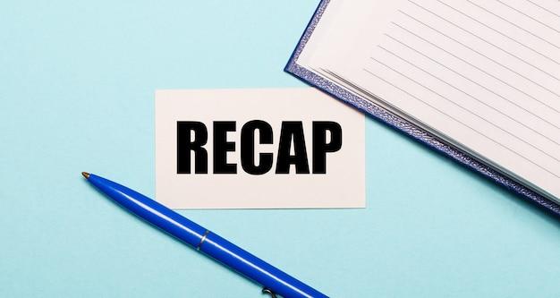 파란색 표면에 비문 recap가있는 메모장, 흰색 펜 및 카드