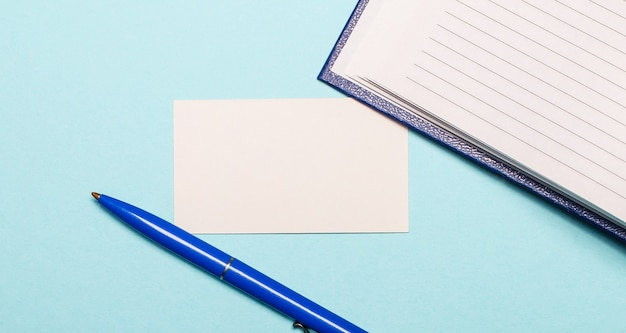 Notepad, white pen and blank card for inserting text or illustrations on a light blue wall. top view with copy space