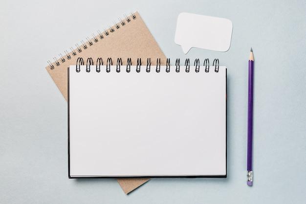 Блокнот, белая наклейка и ручка на столе. копируйте в копировальном пространстве офиса фоне. важно не забыть записку