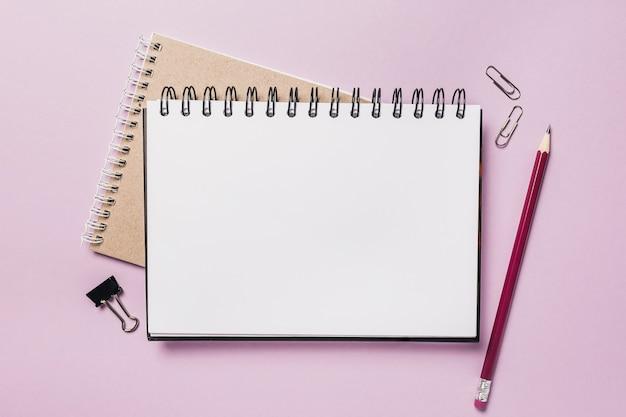 机の上のメモ帳、白いステッカーと鉛筆。コピースペースオフィス紫の背景でモックアップ。注意を忘れないことが重要です