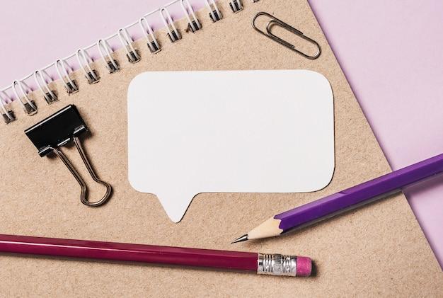 机の上のメモ帳、白いステッカーと鉛筆