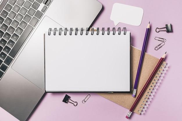 Блокнот, белая наклейка, ноутбук и ручка на столе. копируйте в офисе копирования пространство фиолетовый фон. важно не забыть записку