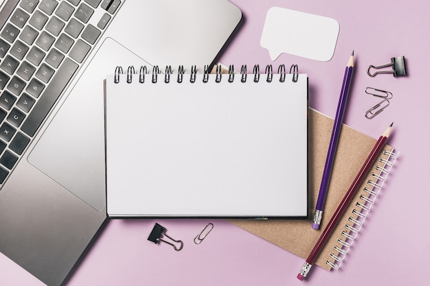 Notepad, white sticker, laptop and pensil on the desk. mock up in copy space office purple background. it is important not to forget the note
