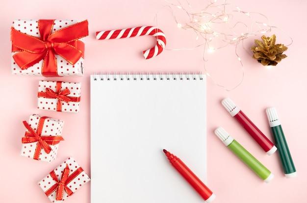 Список желаний блокнота на розовом столе с фломастерами на новогоднем фоне. концепция рождества, нового года, планы и загадывать желания