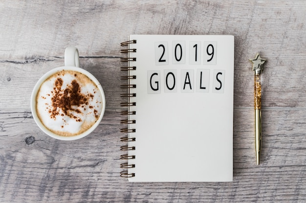 Notepad with 2019 goals inscription on table