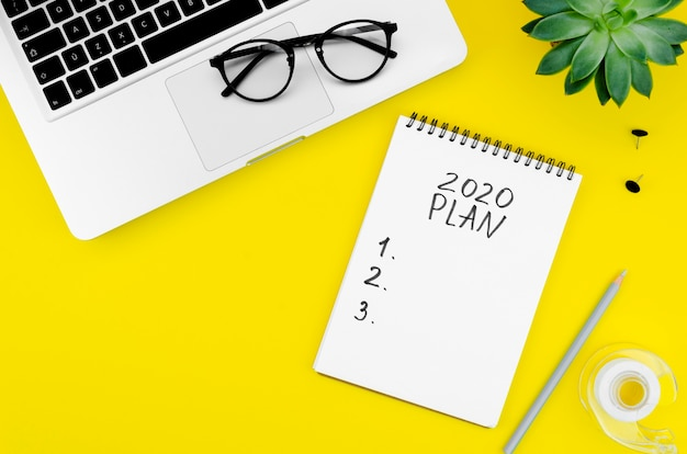 Notepad with 2020 resolutions on yellow background