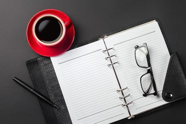 Блокнот с местом для вашей надписи и чашкой кофе с черными очками на рабочем столе. вид сверху. фото высокого качества