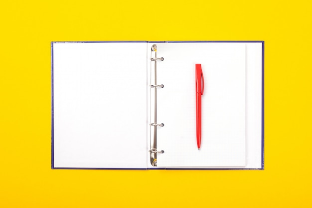 Notepad with ballpoint pen isolated on yellow background