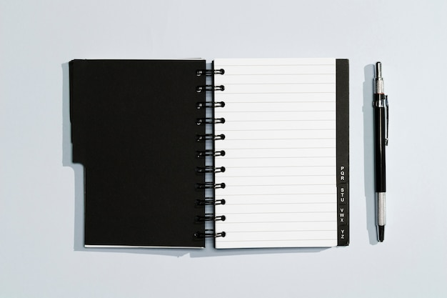 Notepad with black covers and pen