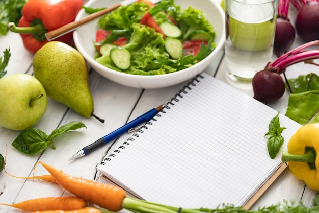 Блокнот с пустыми страницами, миской свежего салата и ингредиентами для здоровой, чистой пищи. написать план диеты, концепция здорового образа жизни