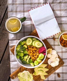Notepad with blank pages and plate of healthy balanced vegetarian food top view. diet food