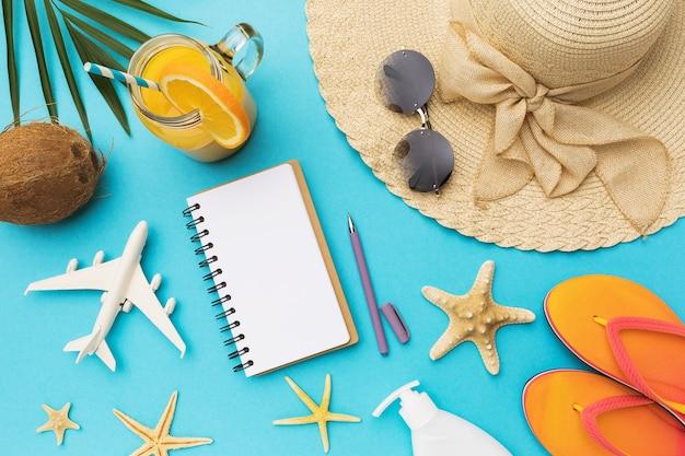 파란색 배경에 휴식을위한 장난감 비행기 및 다양한 액세서리 옆에 텍스트 복사 공간이있는 메모장