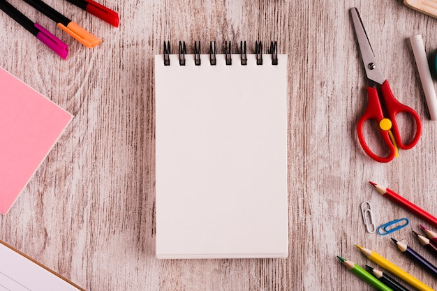 Notepad with drawing set on wooden surface