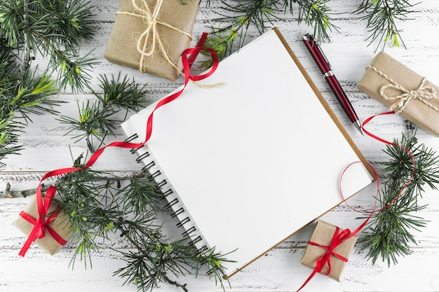 Notepad with fir tree branches on wooden table
