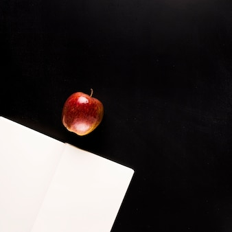Notepad with fruit on black desk