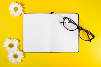 Notepad with glasses and white flowers