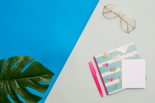 Notepad with glasses and leaf