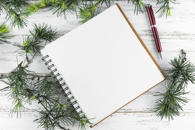 Notepad with green fir tree branches