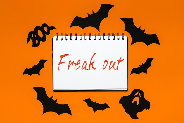 Notepad with halloween text freak out on white and orange background