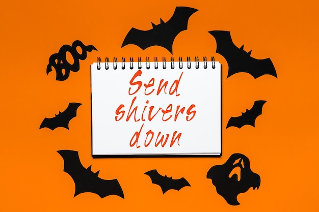 Notepad with halloween text send shivers down on white and orange background