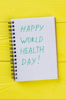 Notepad with happy world health day wish. yellow wooden table background.
