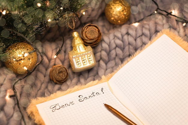 Notepad with the inscription dear santa on a gray knitted background with christmas decorations, top view