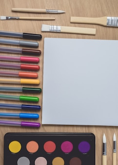 Notepad with many colorful pens and paintbrush on brown wood table