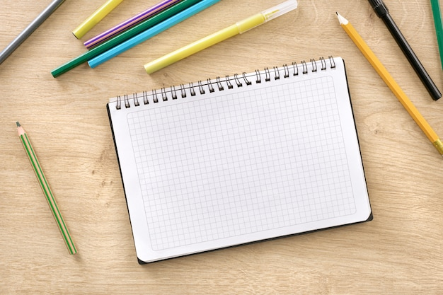 Notepad with markers and pencils on wooden background top view