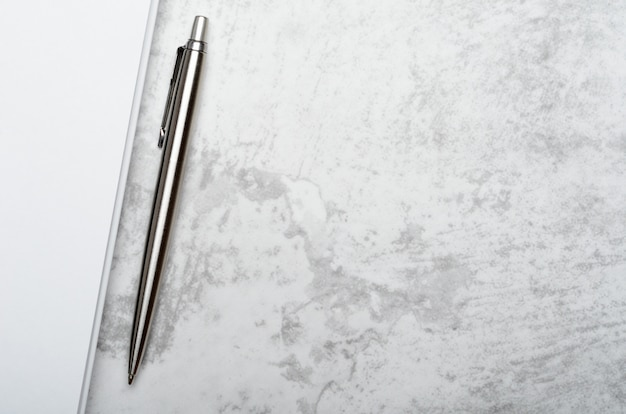 Notepad with metal gray pen on a stone background.
