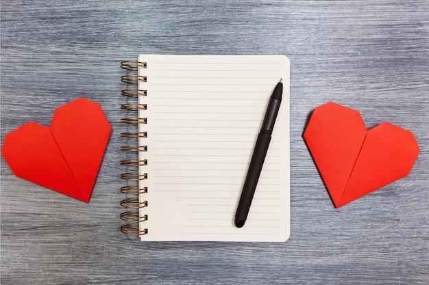 다양한 색상의 하트와 펜이 있는 메모장이 탁자 위에 놓여 있습니다. 마음으로 메모장입니다.