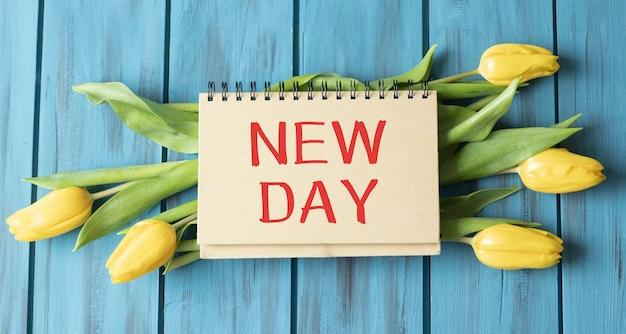 青い木製の背景に黄色い花と新しい日のテキストのメモ帳