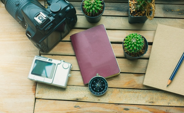 Notepad with passport, camera and smartphone on wood