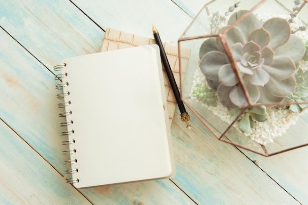 テーブルの上の花とペンでメモ帳。ビジネスコンセプト。コピースペース、セレクティブフォーカス