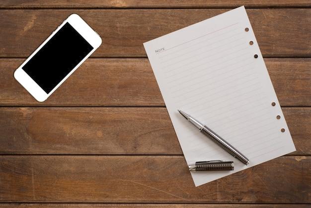 ペンとオフィスの木製のテーブルにスマートフォンとメモ帳。