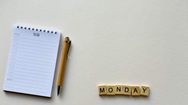 Блокнот с ручкой и деревянным словом «понедельник»