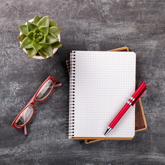 Notepad with pen, glasses , and flower . business concept