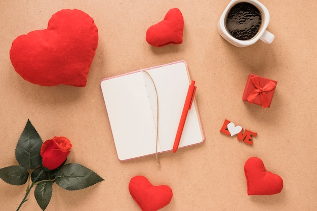 Notepad with pen near ornament hearts, flower and cup of drink