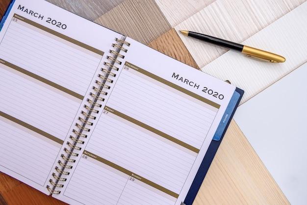 木製のサンプラーにペンでメモ帳をクローズアップ