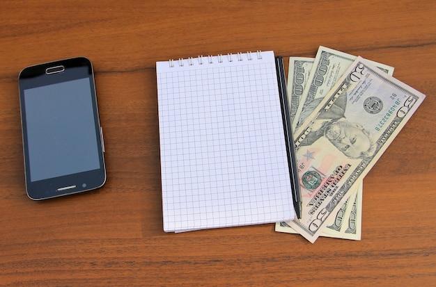 Блокнот с ручкой, смартфоном и долларами на деревянном столе