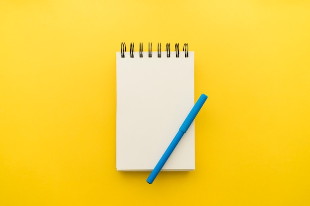 Notepad with pen on yellow background
