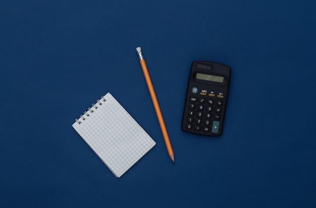 古典的な青い背景に鉛筆とスマートフォンでメモ帳。現代のガジェット。カラー2020。上面図。