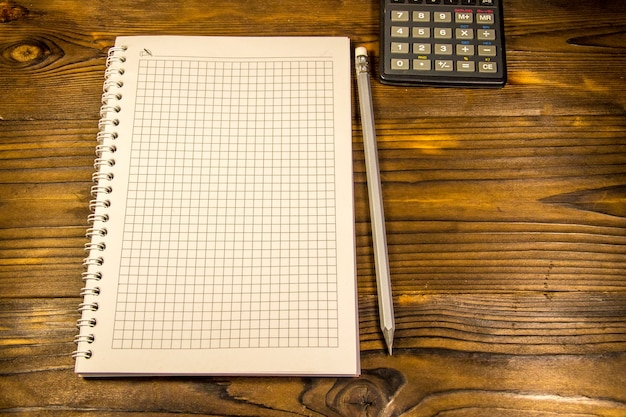 Notepad with pencil and calculator on the wooden desk
