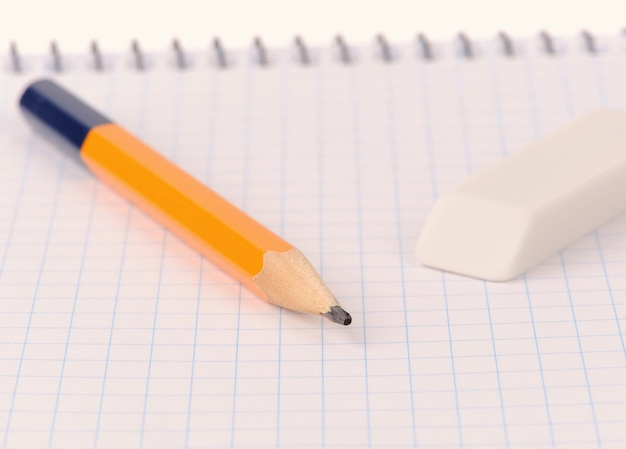 Notepad with pencil and eraser isolated over white background