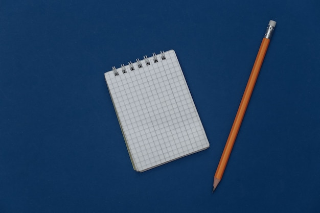 古典的な青い背景に鉛筆でメモ帳。現代のガジェット。カラー2020。上面図。
