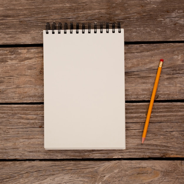 나무 보드 배경에 연필로 메모장